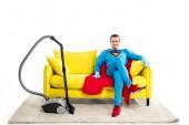 Fotografie lächelnde männlichen Superhelden in Gummihandschuhe auf Sofa in der Nähe von Staubsauger sitzen und Blick in die Kamera, die isoliert auf weiss
