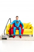 Fotografie superman with vacuum cleaner sitting on couch and looking at camera on white