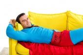 szép ember a szuperhős jelmezben pihent a kanapén, és mosolyogva elszigetelt fehér kamera