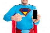 az ember a mutató ujjával a smartphone elszigetelt fehér üres képernyő a szuperhős jelmezben levágott lövés
