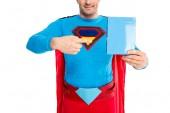 Fotografie zugeschnittenen Schuss von lächelnden Superman zeigt mit Finger auf leeres Feld mit Reinigungsmittel isoliert auf weiss