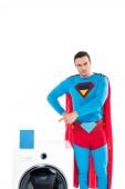 schöner Superheld, der mit dem Finger auf Waschmaschine und Seifenpulver zeigt