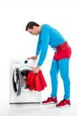 Fotografie lächelnd Superman Waschen von Kleidung in der Waschmaschine auf weiß