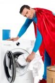 Fotografie Superman praní oblečení v pračce a při pohledu na fotoaparát na bílém