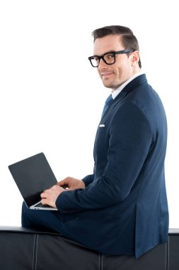 Businessman in suit and eyeglasses using laptop with blank screen and looking at camera isolated on white stock vector