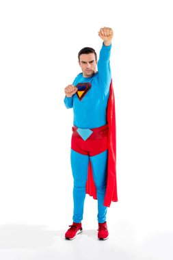 full length view of handsome male superhero raising hand and looking at camera on white