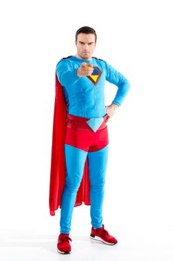 full length view of confident male superhero standing with hand on waist and pointing at camera isolated on white