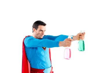 confident superhero holding plastic spray bottles with cleaning liquid and looking away isolated on white