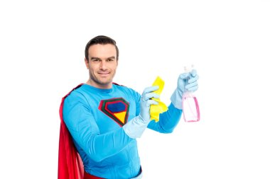 handsome smiling superman holding rag and spray bottle with detergent isolated on white
