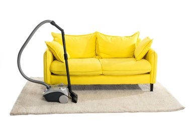 bright yellow sofa and vacuum cleaner on carpet isolated on white