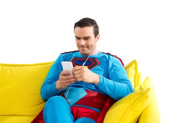 Smiling superman in earphones sitting on sofa and using smartphone isolated on white stock vector