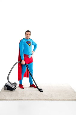 confident superman cleaning carpet with vacuum cleaner and looking at camera isolated on white