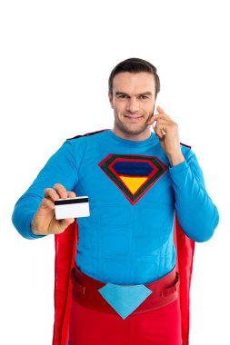 smiling male superhero talking by smartphone and holding credit card isolated on white