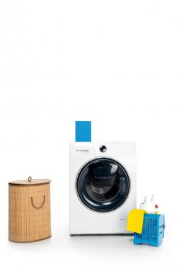 blank box with detergent on washing machine, cleaning supplies and laundry basket isolated on white