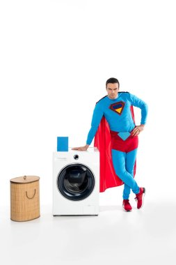 handsome male superhero leaning at washing machine and looking at camera on white