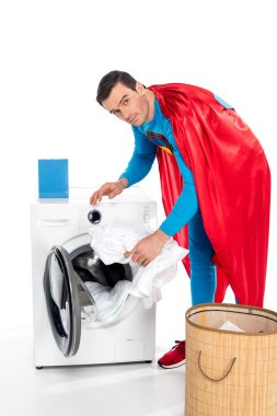 superman washing clothes in washing machine and looking at camera on white