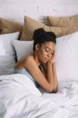 atraktivní africká americká dívka spí na polštáři v posteli