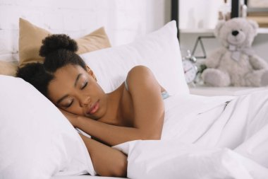 attractive african american young woman sleeping in bedroom