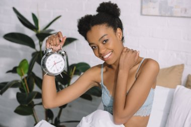cheerful afro girl holding alarm clock in bed in morning