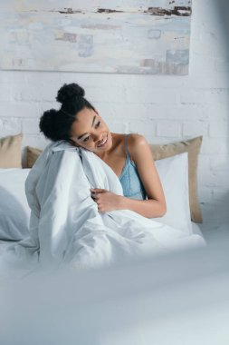 young smiling african american woman sitting in bed in morning