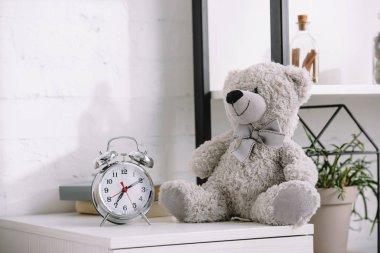 alarm clock and grey teddy bear on nightstand