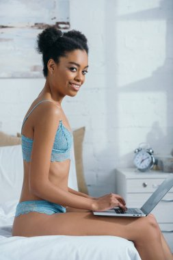 smiling african american girl in lingerie using laptop on bed
