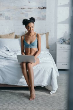 happy african american girl in lingerie using laptop in bedroom in morning