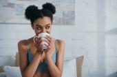 Fotografie atraktivní usměvavá afro dívka pití kávy