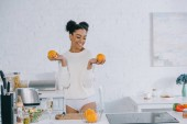 beautiful young woman with fresh healthy oranges at kitchen