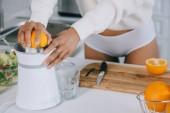 oříznutý snímek ženy ve spodním prádle a svetr mačkání Čerstvý pomerančový džus v kuchyni