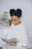Fotografie šťastná mladá žena čtení knihy během přestávky na kávu doma