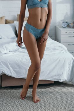 cropped view of slim african american girl in lingerie standing near bed