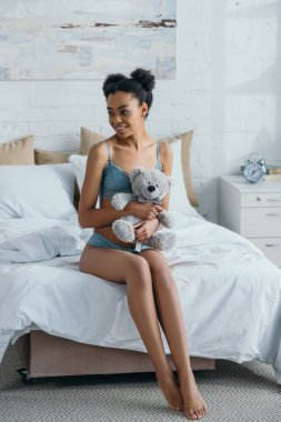 happy african american girl in lingerie holding teddy bear in bedroom in morning