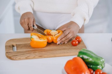 cropped shot of woman slicing bell pepper for salad at kitchen