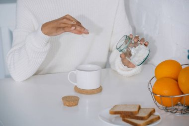 cropped shot of woman adding sugar to her coffee at home