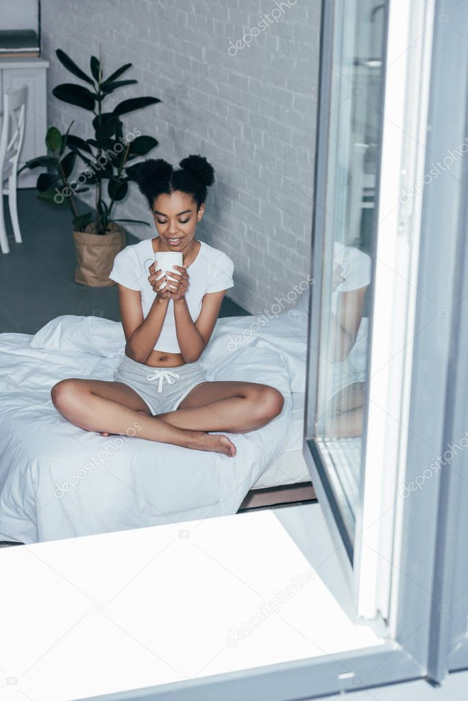 happy young woman sitting on bed at home and drinking hot coffee