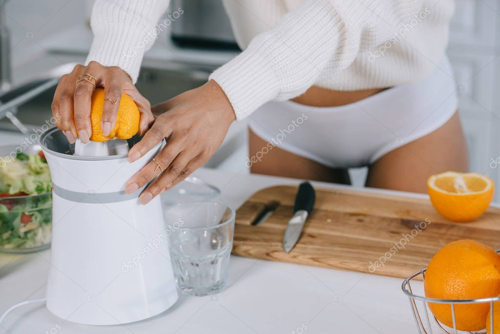 cropped shot of woman in underwear and sweater squeezing fresh orange juice at kitchen