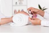 částečný pohled ženy přijímání manikúru od kosmetičky s nehty u stolu s květinami a ručník v salonu krásy