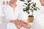 immagine potata di manicure guardando le mani di donna al tavolo nel salone di bellezza