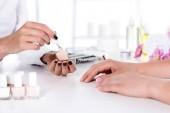 oříznutý snímek ženy přijímání manikúru od kosmetičky s nehty u stolu s květinami a ručník v salonu krásy