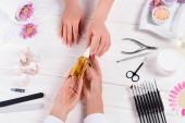 vista parziale della donna prendendo la bottiglia di olio aroma dalle mani di manicure al tavolo con smalti per unghie, lime per unghie, nail clippers, Spingipelle, sale marino, fiori, crema e campioni di smalti per unghie