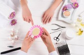 Fotografie top view of woman pointing on samples of nail varnishes in hands of manicurist at table with nail polishes, nail files, nail clippers, cuticle pusher, sea salt, flowers, aroma oil bottles and samples of nail varnishes