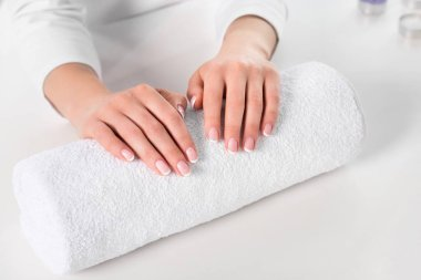 cropped image of woman holding hands for manicure procedure at table with towel in beauty salon