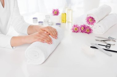 partial view of woman holding hands at table with towels, flowers, candles, aroma oil bottles and instruments for manicure in beauty salon