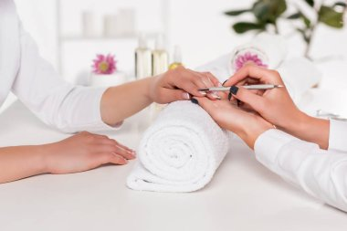 cropped shot of woman receiving manicure by beautician with cuticle pusher at table with flowers and towels in beauty salon