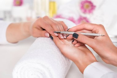 close up image of  woman receiving manicure by beautician with cuticle pusher at table with flowers and towels in beauty salon