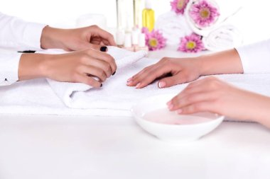 cropped image of manicurist rolling towel to dry hand of woman while she having bath for nails in beauty salon