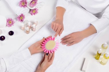 top view of manicurist holding samples of nail varnishes while woman pointing by finger at table with aroma oil bottles, candles, towels, flowers and nail polishes in beauty salon