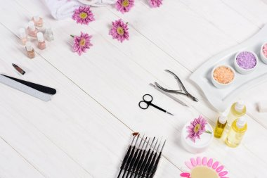 elevated view of flowers, nail polishes, nail files, scissors, cuticle pusher, nail clippers, aroma oil bottles, sea salt, cream, tools for manicure and samples of nail varnishes at table