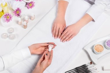 cropped image of manicurist showing nail polish to woman at table with candles, sea salt, flowers, aroma oil bottles, towels and tools for manicure